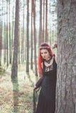 Härlig kvinnahäxa med rött hår i skogen Arkivbild