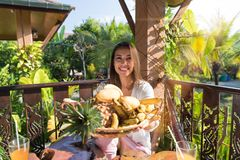 Härlig kvinnahållplatta av läckra frukter för lycklig le ung flicka för frukost på sommarterrass i tropiskt Arkivbilder