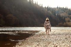 Härlig kvinnahipster som går på flodstranden i berg, den bärande hatten och ponchon, boholoppbegrepp, utrymme för text royaltyfri bild
