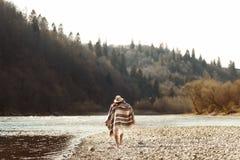 Härlig kvinnahipster som går på flodstranden i berg, kläder royaltyfri foto