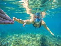 Härlig kvinnainnehavhand som snorklar under vatten royaltyfria bilder