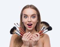 Härlig kvinnainnehavuppsättning av sminkborstar arkivfoto