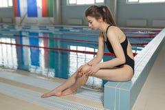 Härlig kvinnakänsla smärtar i hennes fot på simbassängen Sportar som övar skada royaltyfri foto