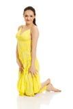 Härlig kvinnakneelin i gul klänning Royaltyfri Fotografi