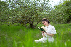 Härlig kvinnaläsebok på sommaräng Arkivbild
