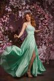 Härlig kvinnamodell i enfärgad klänning på en blommig vårbakgrund Skönhetflicka med en bedöva makeup och frisyr arkivbilder