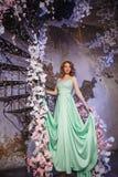 Härlig kvinnamodell i enfärgad klänning på en blommig vårbakgrund Skönhetflicka med en bedöva makeup och frisyr royaltyfri fotografi