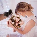 härlig kvinnamodell med ny daglig makeup och romantiska krabba frisyren som rymmer en bukett av blommor royaltyfri fotografi