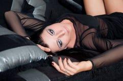 Härlig kvinnamodell som ligger i svart klänninginre royaltyfri foto