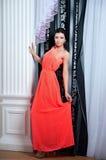 Härlig kvinnamodell som poserar i elegant röd klänning arkivfoto