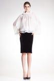 Härlig kvinnamodell som poserar i elegant vit blus och svart klänning Arkivbilder