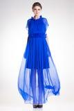 Härlig kvinnamodell som poserar i lång elegant blå siden- klänning Arkivbilder