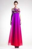 Härlig kvinnamodell som poserar i lång färgrik klänning med fjädrar royaltyfria foton