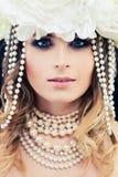 Härlig kvinnamodemodell med pärlor och blommor Gla Royaltyfria Foton