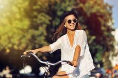 Härlig kvinnaridning på cykeln Arkivbild