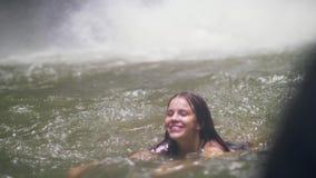Härlig kvinnasimning i bergsjön och vattenfärgstänk på bakgrund Turist- kvinna som badar i sötvatten från stock video