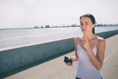 Härlig kvinnaspring under solnedgång Ung konditionmodell nära sjösidan Iklädd sportswear arkivbild