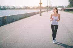 Härlig kvinnaspring under solnedgång Ung konditionmodell nära sjösidan Iklädd sportswear arkivfoton