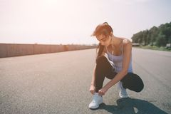 Härlig kvinnaspring under solnedgång Ung konditionmodell nära sjösidan Iklädd sportswear Binder med rep gymnastikskor royaltyfri foto