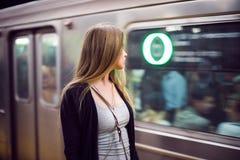 Härlig kvinnaställning på gångtunnelstationen som ser det ankommande tunnelbanadrevet arkivbilder