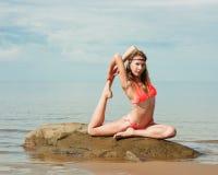 Härlig kvinnayoga på stranden royaltyfria foton