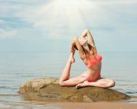 Härlig kvinnayoga på stranden arkivfoto