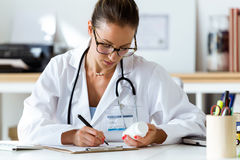 Härlig kvinnlig apotekareinnehavkrus av preventivpillerar i händer fotografering för bildbyråer