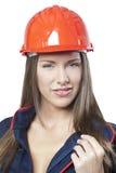 Härlig kvinnlig arbetare i blå overall och röd säkerhetshjälm royaltyfria bilder