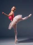 Härlig kvinnlig balettdansör på en grå färg arkivfoto