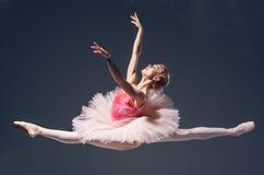 Härlig kvinnlig balettdansörbanhoppning på en grå färg royaltyfria foton