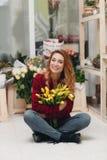 Härlig kvinnlig blomsterhandlare i blomsterhandel arkivbilder