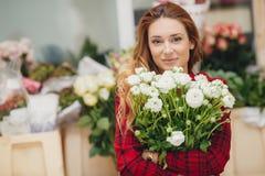 Härlig kvinnlig blomsterhandlare i blomsterhandel arkivfoton