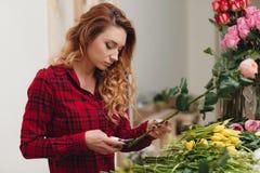 Härlig kvinnlig blomsterhandlare i blomsterhandel fotografering för bildbyråer