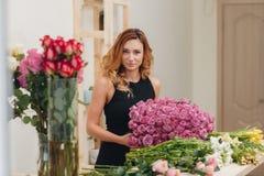 Härlig kvinnlig blomsterhandlare i blomsterhandel royaltyfri fotografi