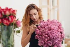 Härlig kvinnlig blomsterhandlare i blomsterhandel royaltyfri foto