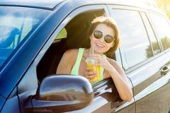 Härlig kvinnlig chaufför som ler, medan köra hans bil fotografering för bildbyråer