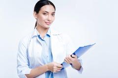 Härlig kvinnlig doktor som poserar med en arkH-hållare royaltyfri fotografi