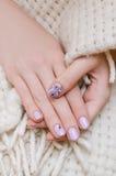 Härlig kvinnlig hand med ljus - lilor spikar design arkivfoto