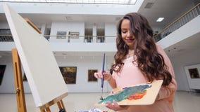 Härlig kvinnlig konstnärmålning med olje- målarfärger stock video