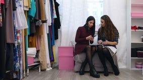 Härlig kvinnlig kundshow en klänning som hon önskar att beställa till boutiqueägaren som använder mobiltelefonen stock video