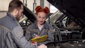Härlig kvinnlig mekaniker och hennes undersökande motor för manlig kollega av en bil lager videofilmer