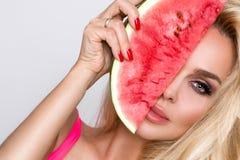 Härlig kvinnlig modell med långt blont hår som rymmer en vattenmelon royaltyfria foton