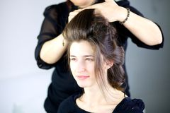 Härlig kvinnlig modell som får hår gjort av den yrkesmässiga frisören Fotografering för Bildbyråer