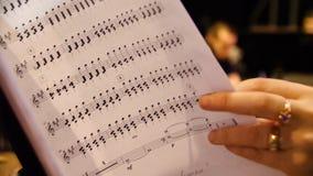 Härlig kvinnlig musikkompositör som ser musikanmärkningar Kvinnan ser anmärkningar på pianocloseupen Arkivbild