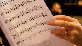 Härlig kvinnlig musikkompositör som ser musikanmärkningar Kvinnan ser anmärkningar på pianocloseupen Royaltyfria Foton