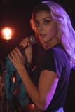 Härlig kvinnlig sångare som sjunger i upplyst nattklubb Fotografering för Bildbyråer