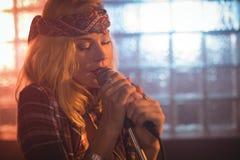 Härlig kvinnlig sångare som utför i upplyst nattklubb Royaltyfria Bilder
