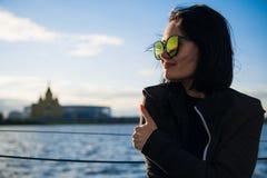 Härlig kvinnlig som tycker om hennes fria tid vid floden Utomhus- livsstil för flicka Ung kvinna med att bära för svart hår arkivbilder