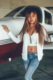Härlig kvinnlig stående i flygplanhangaren, med modern ai Royaltyfria Foton