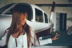 Härlig kvinnlig stående i flygplanhangaren, med modern ai Royaltyfri Fotografi